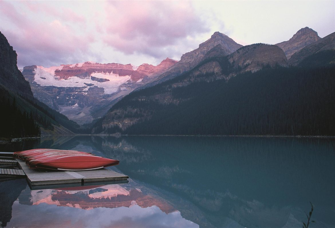 twilight hour at Lake Louise giving the mountains a pink hue with canoe sin the foreground